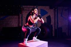 Femme convenable attirante de Moyen Âge faisant la boîte sautant à un style de crossfit L'athlète féminin exécute des sauts au gy photographie stock
