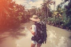 Femme convenable avec le sac à dos se tenant près de la grande rivière tropicale et regardant loin Images libres de droits