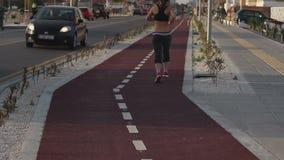 Femme convenable courant une voie pulsante le long de rue de ville, forme physique extérieure, vêtements de sport banque de vidéos
