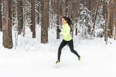 Femme convenable d'athlète de jeunes courant à la forêt sprintant pendant la formation d'hiver dehors par temps froid de neige image stock