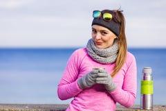 Femme convenable dans le jour froid réchauffant le thé de boissons images stock