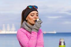 Femme convenable dans le jour froid réchauffant le thé de boissons Images libres de droits