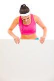 Femme convenable dans les vêtements de sport regardant sur le panneau-réclame blanc Photos libres de droits