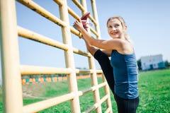 Femme convenable de jeunes dans une chemise bleue et des guêtres s'exerçant dehors au coucher du soleil Femme de forme physique f Photo stock