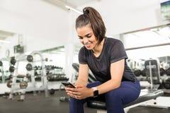Femme convenable de sourire à l'aide du téléphone intelligent dans le club de santé photographie stock