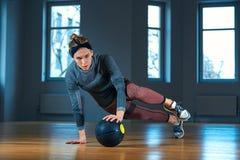 Femme convenable et musculaire faisant la séance d'entraînement intense de noyau avec le kettlebell dans le gymnase Exercice feme image libre de droits