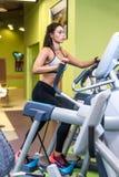 Femme convenable faisant l'exercice sur un entraîneur elliptique Images stock