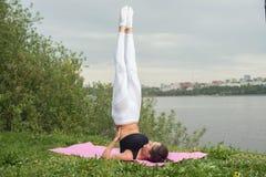 Femme convenable faisant le yoga dans la pose de shoulderstand s'exerçant en nature Images stock