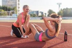 Femme convenable faisant reposer-UPS tandis qu'un ami affermit ses pieds Craquements d'ABS avec l'aide d'associé au stade Image libre de droits