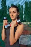 Femme convenable fraîche posant avec des haltères dans le stade dans le jour ensoleillé L'espace vide images libres de droits