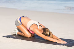 Femme convenable l'étirant de retour sur le tapis d'exercice Photo stock