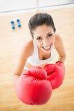 Femme convenable portant les gants de boxe rouges souriant à l'appareil-photo Photos stock
