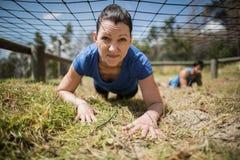 Femme convenable rampant sous le filet pendant le parcours du combattant photographie stock