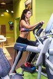Femme convenable s'exerçant à la séance d'entraînement elliptique d'entraîneur de marcheur d'aérobic de gymnase de forme physique Photos stock
