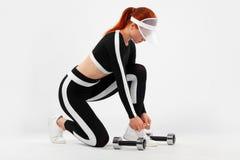 Femme convenable sportive, athlète avec des haltères prepearing à la forme physique s'exerçant sur le fond blanc photo stock