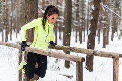 Femme convenable travaillant avec propres triceps et biceps de séance d'entraînement de poids corporel sur les barres horizontale Image stock
