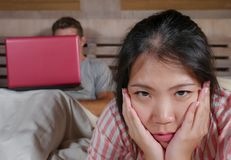Femme coréenne frustrée dans le lit ignoré par la mise en réseau sociale d'ami de mari de bourreau de travail ou d'intoxiqué de m image stock