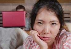 Femme coréenne frustrée dans le lit ignoré par la mise en réseau sociale d'ami de mari de bourreau de travail ou d'intoxiqué de m photos stock