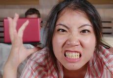 Femme coréenne frustrée dans le lit ignoré par la mise en réseau sociale d'ami de mari de bourreau de travail ou d'intoxiqué de m photographie stock libre de droits