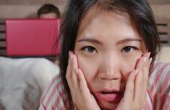Femme coréenne frustrée dans le lit ignoré par la mise en réseau sociale d'ami de mari de bourreau de travail ou d'intoxiqué de m photographie stock