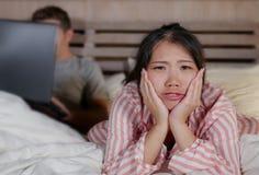 Femme coréenne frustrée dans le lit ignoré par la mise en réseau sociale d'ami de mari de bourreau de travail ou d'intoxiqué de m image libre de droits