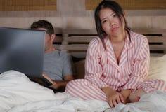Femme coréenne frustrée dans le lit ignoré par la mise en réseau sociale d'ami de mari de bourreau de travail ou d'intoxiqué de m photo stock