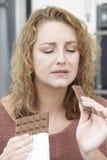 Femme coupable sur le régime mangeant la barre de chocolat à la maison Photos stock