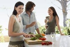 Femme coupant des légumes avec des amis communiquant au comptoir de cuisine Photo libre de droits