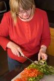 Femme coupant des poivrons. Photo stock