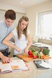 Femme coupant des poivrons avec le livre de cuisine de lecture de l'homme Photos stock