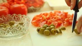 Femme coupant en tranches des olives pour une salade clips vidéos