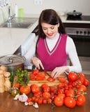 Femme coupant en tranches des tomates Photographie stock libre de droits