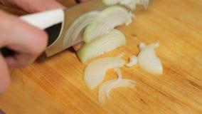 Femme coupant en tranches l'oignon pour la pizza couper en tranches l'oignon dans la cuisine Oignon de coupe de femme sur une pla clips vidéos