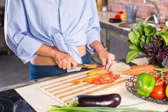 Femme coupant en tranches la carotte sur le panneau de cuisine Photo libre de droits