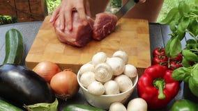 Femme coupant en tranches la viande sur un conseil en bois banque de vidéos