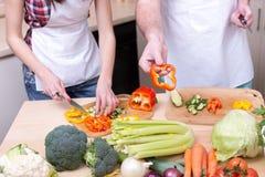 Femme coupant en tranches les légumes et le poivre d'offre d'homme Image libre de droits