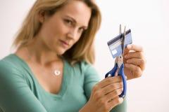 Femme coupant par la carte de crédit Photos libres de droits