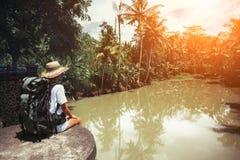 Femme courageuse avec le sac à dos se reposant près de la grande rivière tropicale et regardant loin Images libres de droits
