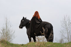 Femme courageuse avec les cheveux rouges dans le manteau noir sur le cheval frison Photo stock