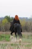 Femme courageuse avec les cheveux rouges dans le manteau noir sur le cheval frison Image stock