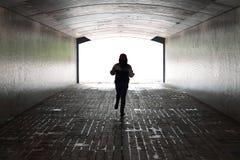 Femme courant à l'intérieur d'un tunnel Photo stock
