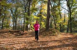Femme courant dans la forêt Photographie stock libre de droits