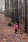Femme courant dans la formation en bois de forêt images stock