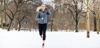 Femme courant en bas d'un chemin le jour d'hiver en parc Image stock