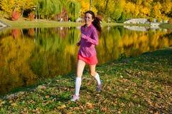 Femme courant en parc d'automne, beau coureur de fille pulsant dehors Image stock