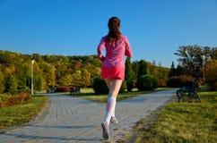Femme courant en parc d'automne, beau coureur de fille pulsant dehors Images libres de droits