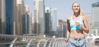 Femme courant ou pulsant au-dessus de la rue de ville du Dubaï Photos stock