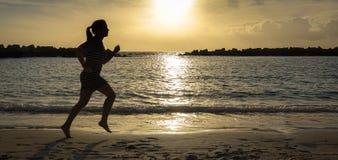 Femme courant sur la plage au coucher du soleil image libre de droits