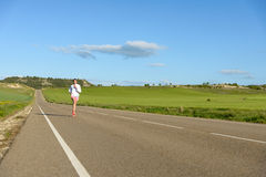 Femme courant sur la route de campagne Photo stock