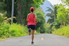 Femme courant sur la traînée tropicale de forêt de matin Image stock